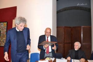 L'avv. Limuti guarda compiaciuto la targa consegnatagli dall'avv. Iacona
